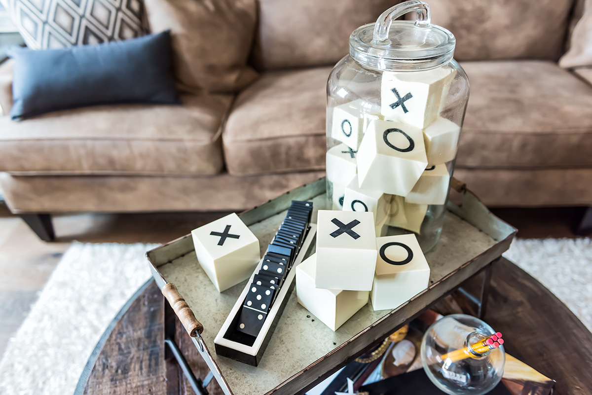 Game room tray stand with x and o, dominoes, on coffee table in staging model house or apartment by brown leather couch